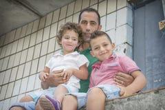 Im Sommer sitzt der Vater auf der Straße und umarmt die Tochter a Lizenzfreie Stockfotografie