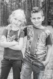 Im Sommer im Wald umarmt ein kleiner Junge das Mädchen Stockbild