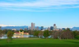 Im Stadtzentrum gelegene panoramische Skylinegebäude Denvers mit schneebedeckten Bergen und Bäumen Lizenzfreies Stockfoto