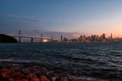 Im Stadtzentrum gelegene San Francisco- und Bucht-Brücke an der Dämmerung Lizenzfreies Stockbild