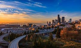 Im Stadtzentrum gelegene Skyline und Wolkenkratzer Seattles über dem I-5 I-90 Autobahnaustausch bei Sonnenuntergang im Fall mit g lizenzfreie stockfotos