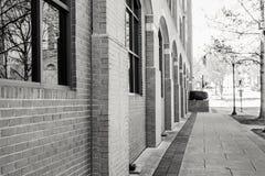 Im Stadtzentrum gelegener Stadt-Gehweg entlang einem Backsteinbau Stockfotografie