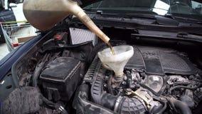 Im Tankstellemechaniker durch einen Trichter gießen Sie Öl in einem Automotor stock footage