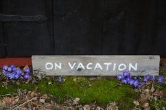 Im Urlaub Zeichen durch blaue Blumen Lizenzfreie Stockfotografie