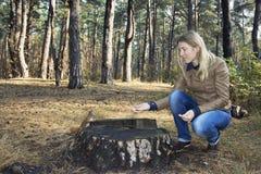 Im Wald nahe Stumpf zieht das Mädchen ein Eichhörnchen mit Nüssen ein Lizenzfreies Stockbild
