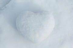 Im Winter cobbled die weißen Schneelügen zusammen einen Schneeball in Form eines Herzens Auf der Straße ist der Tag und die Sonne Lizenzfreie Stockfotos