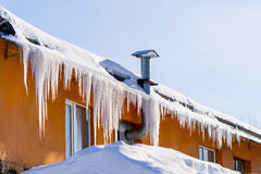 Im Winter hängen die Eiszapfen an einem Gebäudedach Stockfotos