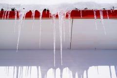 Im Winter hängen die Eiszapfen an einem Gebäudedach Stockbild