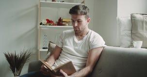 Im Wohnzimmermann, der im Sofa sitzt und herum ein Buch, moderner Entwurf liest stock footage