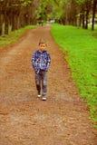 Im zich verheugt op de toekomst Weinig jongen geniet van een rooskleurigere toekomst Weinig jongensgang langs voetpad in park pre royalty-vrije stock foto's