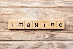 Imagínese la palabra escrita en el bloque de madera imagínese el texto en la tabla, concepto fotografía de archivo libre de regalías