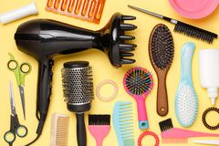 Image accessories of hairdresser, hair dryer, combs. On empty yellow background royalty free stock photo
