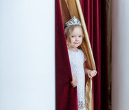 Image of adorable girl posing looking out curtains Stock Images