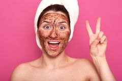 Image of adorable magnetic half naked lady raising two fingers, opening her mouth in sincere smile, posing with brown mask on her stock image