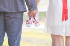 An image of adults holding baby pair of sneakers in red. Pregnancy and expectation. Stock Photos