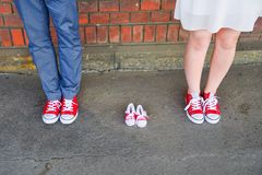 An image of adults in red sneakers next to baby pair of sneakers. Pregnancy and expectation concept. Royalty Free Stock Photography