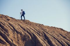 Image from afar from back of man with backpack and walking sticks royalty free stock photo
