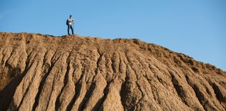 Image of afar of male tourist with sticks for walking on hill against blue sky stock images