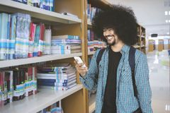 African man using a smartphone in the library. Image of African man looks happy while using a smartphone and standing in the library Stock Image
