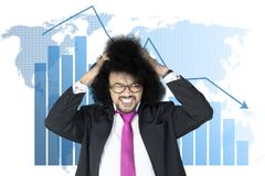 Stressful Afro businessman with declining arrow Stock Photo