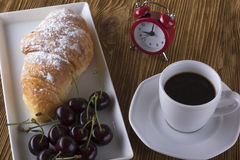 Image of alarm clock, hot coffee and croissant. Royalty Free Stock Photos