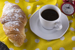 Image of alarm clock, hot coffee and croissant. Royalty Free Stock Image
