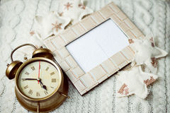 Image of alarm clock on knitted background sorounded with decorative stars Royalty Free Stock Image