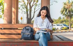 Image of an amazing beautiful woman sitting on a bench in park reading book royalty free stock images