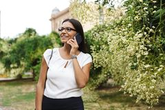 Beautiful business woman walking outdoors talking by mobile phone. Image of amazing pretty business woman walking outdoors talking by mobile phone stock photography