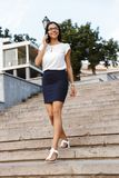 Beautiful business woman walking outdoors talking by mobile phone royalty free stock photography