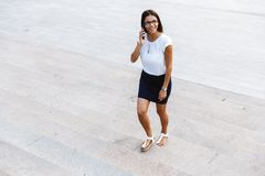 Beautiful business woman walking outdoors talking by mobile phone royalty free stock photo