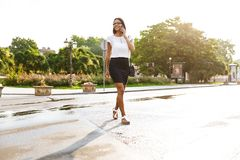Beautiful business woman walking outdoors talking by mobile phone stock image