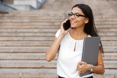 Beautiful business woman walking outdoors talking by mobile phone. Image of amazing pretty business woman walking outdoors talking by mobile phone holing laptop stock photo