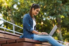 Amazing young beautiful woman sitting outdoors using laptop computer. royalty free stock photography