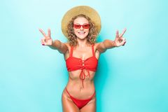 Portrait of amazing young woman showing peace gesture in red bikini isolated over green background. royalty free stock photo