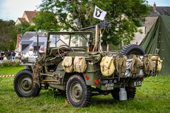 Image of an American army jeep in Normandy in a camp. Recreation on the 70th anniversary. Back view with tourists watching. Metal willys war transport stock photos