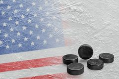 Image of the American flag on ice and hockey pucks. Hockey pucks and the image of the American flag on the ice. Concept, hockey, background Stock Photos
