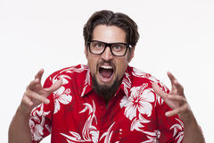 Image of a angry young man in Hawaiian shirt posing against whit stock photography