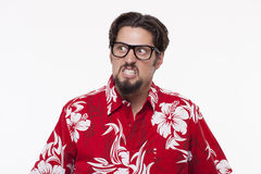 Image of a angry young man in Hawaiian shirt posing against whit. Angry young man in Hawaiian shirt Stock Images