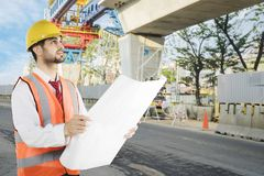Arabian foreman working with a blueprint. Image of Arabian foreman working with a blueprint while standing in the construction site royalty free stock photo
