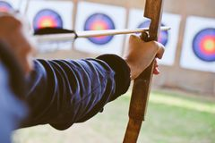 Archer holds his bow aiming at a target Royalty Free Stock Photo