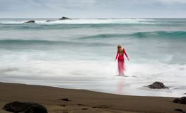 Image artistique de beaux-arts au sujet belle d'une femme blonde habillée rouge et longue, qui se tient sur une roche de plage da photos stock