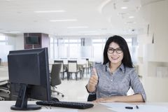 Asian businesswoman showing thumb up. Image of Asian businesswoman working in the office while showing thumb up at the camera Royalty Free Stock Photos