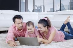 Asian family playing with laptop on the carpet. Image of Asian family playing with a laptop while lying together on the carpet. Shot in the apartment Royalty Free Stock Images