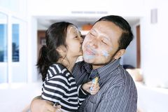 Asian father kissed by his daughter. Image of Asian father kissed by his daughter while playing with crayons in the living room Stock Photography