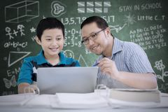Asian teacher guides his student to use a laptop. Image of Asian teacher guides his student to use a laptop while sitting in the classroom Stock Photo