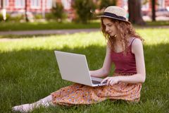 Image of attentive busy student holding her laptop, searching for suitable information, being attentive, sitting on grass at green. Space, having inspiration in royalty free stock photography