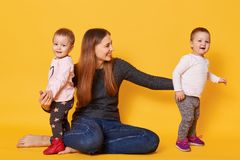 Image of attractive brown haired mother wants to be photographed with her sweet children, sit on floor in studio. Mother and girls stock photo