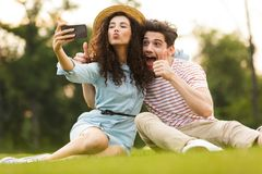 Image of man and woman 20s sitting on green grass in park and taking selfie on smartphone stock photos