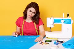 Image of attractive female fashion designer working in her workshop, being in process of creating new clothes collection, tired of stock photography